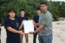 Petty Officer 2nd Class Filberto Noriega receives a letter of appreciation from a high school student from Iwate prefecture Nov. 24, 2019 at Henoko beach. High school students from all over Japan concerning the problem of marine plastic waste visited Camp Schwab to join the Marines of Camp Schwab's Single Marine Program in cleaning Henoko beach. After the beach cleanup, the students presented a certificate of appreciation to Marines who regularly participate beach cleanups in all over Okinawa.
