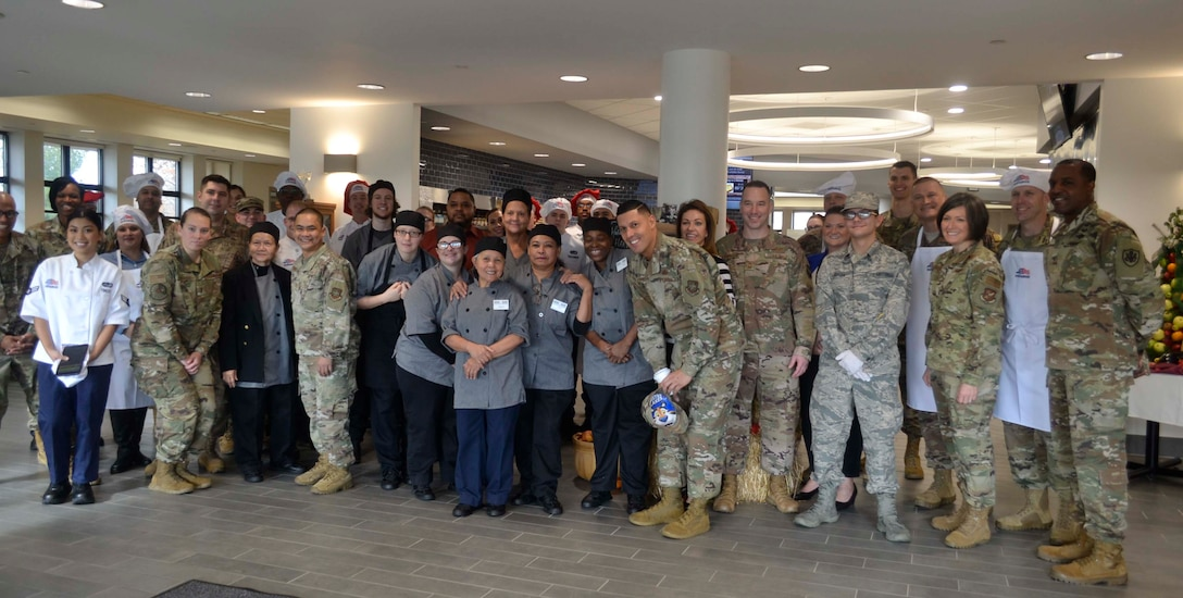 DLA Troop Support Commander Army Brig. Gen. Gavin Lawrence, far right, poses with senior leaders assigned to the 87th Force Support Squadron, Joint Basie McGuire-Dix-Lakehurst, and dining facility staff pose for a photo, before serving the traditional Thanksgiving meal Nov. 28, 2019, at the Halverson Hall Dining Facility, Joint Base McGuire-Dix-Lakehurst, New Jersey. The staff of the Halverson Hall Dining Facility provided the traditional Thanksgiving meal for airmen and their families who were away from home for the holiday. (Photo by Alexandria Brimage-Gray)