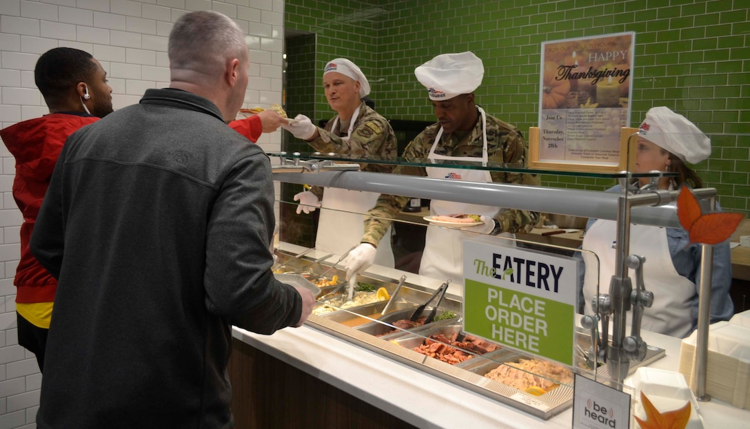 Army Brig. Gen. Gavin Lawrence, DLA Troop Support commander, second from right, serves two airmen a traditional Thanksgiving meal, Nov. 28, 2019, at the Halverson Hall Dining Facility, Joint Base McGuire-Dix-Lakehurst, New Jersey. Lawrence, along with senior leaders assigned to the 87th Force Support Squadron and their spouses, served meals to airmen and their families who were away from home for the holiday. (Photo by Alexandria Brimage-Gray)