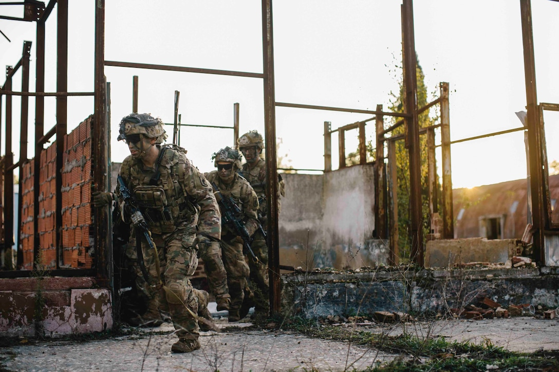 Soldiers run through a damaged building.