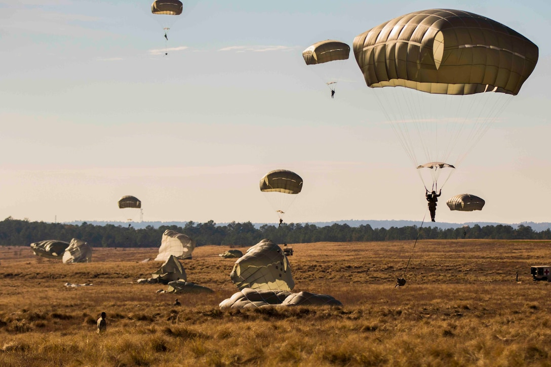 Soldiers wearing parachutes descend from the sky to the ground.