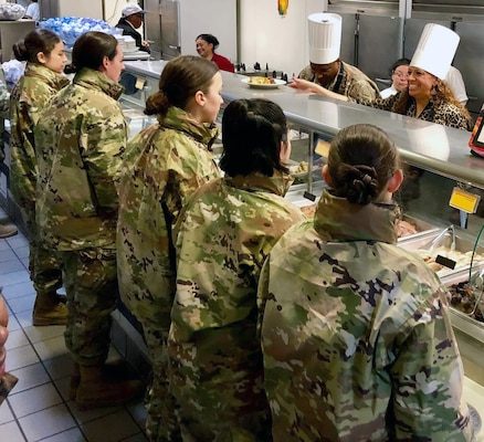 Col. Devin R. Pepper (on line, center), commander, 460th Space Wing, Buckley Air Force Base, Colorado, helps dish out Thanksgiving meals to Airmen in basic training at Joint Base San Antonio-Lackland Nov. 28. Pepper served as the reviewing official at the Air Force Basic Military Training parade Nov. 29.