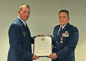 Lt. Col. David Kraft, left, 911th Operations Group deputy commander, presents Lt. Col. Edward Tarquinio, 758th Airlift Squadron pilot, with a certificate of retirement during a retirement ceremony at the Pittsburgh International Airport Air Reserve Station, Pennsylvania, Nov. 3, 2019.