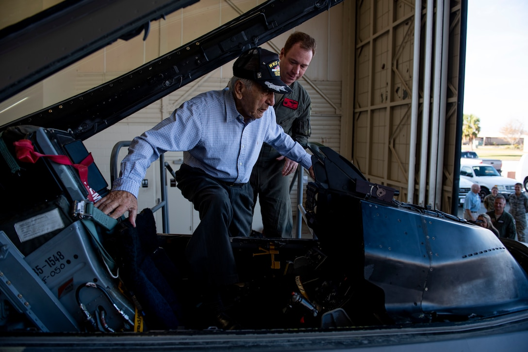 Retired U.S. Air Force Lt. Col. Daniel Daube, left, boards the cockpit of a static QF-16 Fighting Falcon, assisted by U.S. Air Force Lt. Col. Richard Wilson, 325th Operations Support Squadron assistant director of operations, right, at Tyndall Air Force Base, Florida, Nov. 27, 2019. Daube was a veteran of World War II, Korean, and Vietnam war, flying multiple air frames and combat missions. (U.S. Air Force photo by Staff Sgt. Magen M. Reeves)