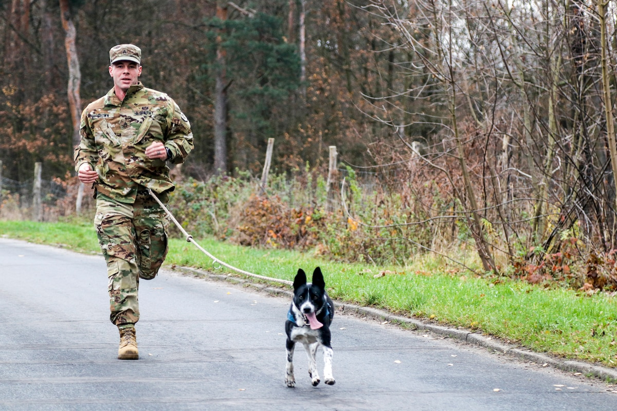 A soldier runs with a small black-and-white dog on a road.