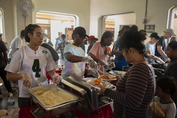 Lt. Klint Johnson, a chaplain assigned to the submarine tender USS Frank Cable (AS 40), picks up trash at the Salvation Army's annual Thanksgiving feast to provide free meals for the Guam community at Chamorro Village,