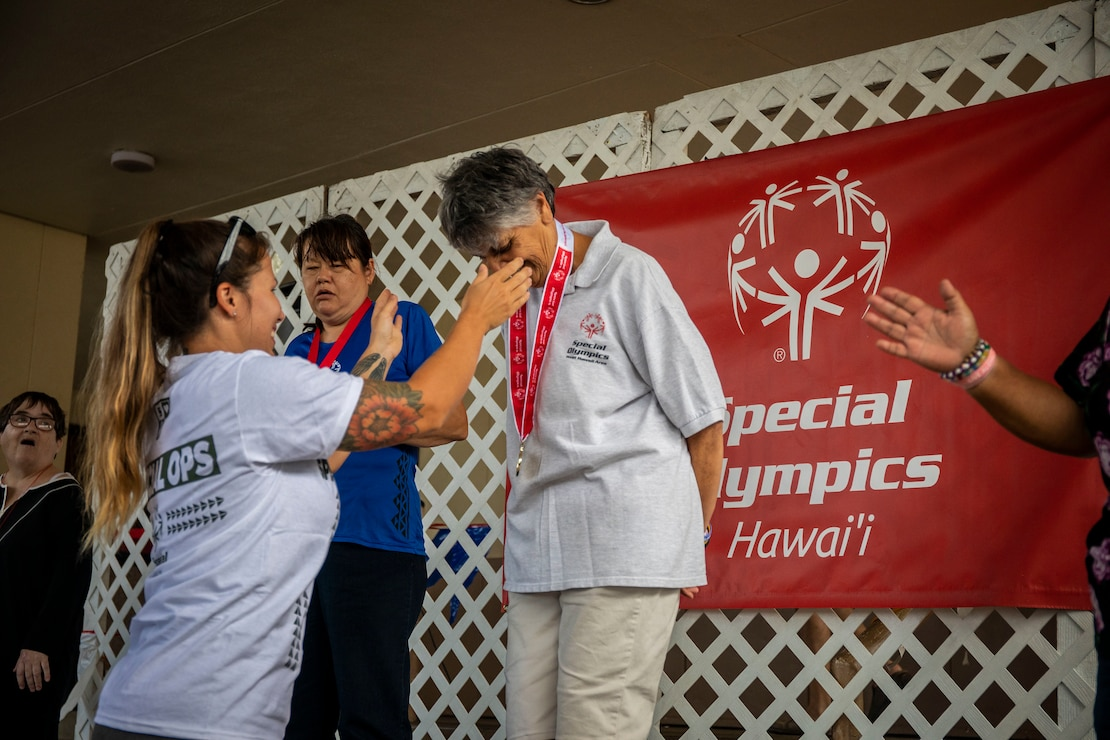 Volunteers present medals to participants during the Special Olympics Hawaii Holiday Classic State Games, Marine Corps Base Hawaii, Nov. 23.