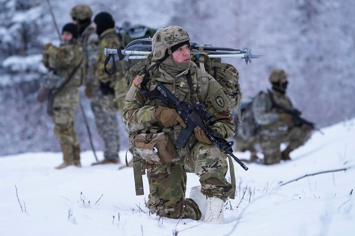 A soldier kneels in snow holding a weapon.