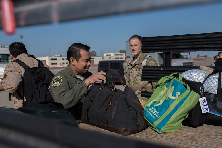 U.S. Air Force Master Sgt. Emmanuel Amigleo, 70th Air Refueling Squadron KC-10 Extender flight engineer, helps a KC-10 crew load their baggage after they return from their deployment Nov. 21, 2019, at Travis Air Force Base, California. The KC-10 crew returned to Travis AFB for the holidays after supporting operations in Southwest Asia for two months. (U.S. Air Force photo by Airman 1st Class Cameron Otte)