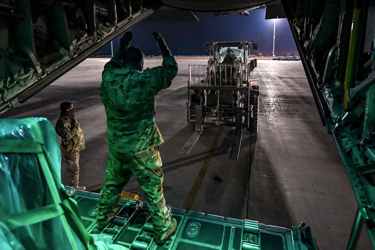 An airman in an open aircraft gestures to a forklift driver on a flightline.