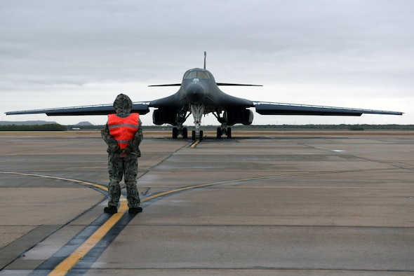 Crew chief marshalls B-1B Lancer aircraft