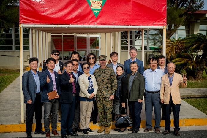 U.S. Marine Corps Col. David Steele, commanding officer of Marine Corps Air Station (MCAS) Futenma takes a group photo with journalists during a base visit on Nov. 7, 2019. MCAS Futenma held the function for journalists visiting from the Republic of Korea to help build and foster friendly relations. (U.S. Marine Corps photo by Lance Cpl. Kindo Go)