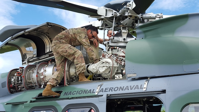 Master Sgt. Raphael Romero, 571st Mobility Support Advisory Squadron aircraft maintenance senior air advisor, performs a post-flight inspection on an Augusta Westland AW-139 helicopter engine along with the National Air and Naval Service of Panama flying crew chief at Nicanor Air Base, Panama. Air advisors assess, train, advise and assist U.S. Southern Command lines of effort of strengthening partnerships and countering threats from transnational criminal organizations. (Courtesy Photo)