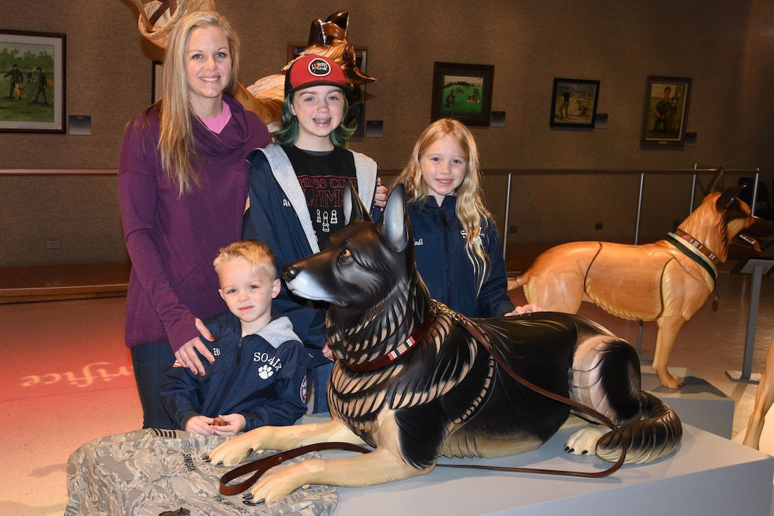 Erin Simpson and family stand with wooden sculpture of their dog Robson at the National Museum of the USAF.