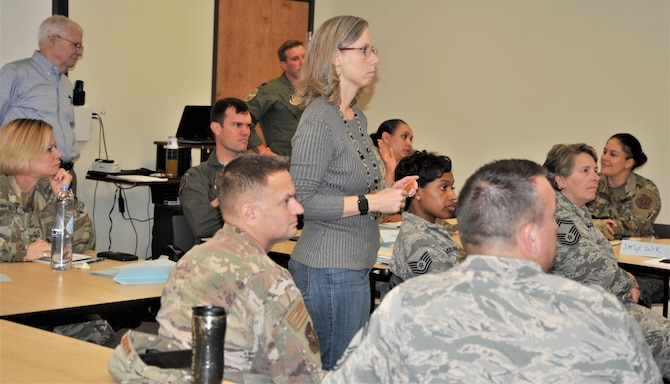 Teresa Davies, 340th Flying Training Group continuous improvement manager, briefs 340th Flying Training Group members gathered at Joint Base San Antonio-Randolph, Texas Nov. 19-21 for a Continuous process improvement event to address pay issues that occur when Reserve members transition between pay statuses as Davies' improvement process mentor, Bob Daffin from the Air Force Reserve Command at Robins Air Force Base, Ga. looks on. (U.S. Air Force photo by Debbie Gildea)