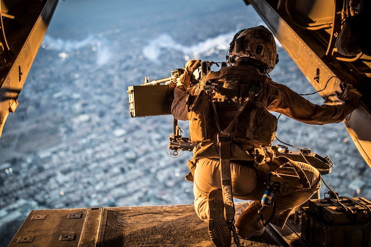 A Marine kneels at the back of an aircraft looking at the horizon.