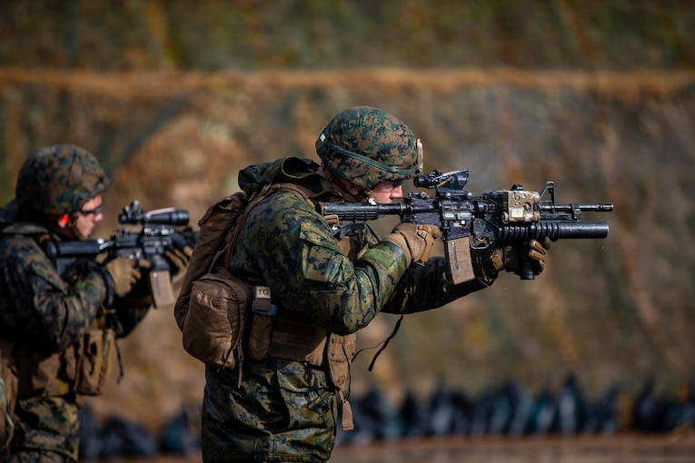 Two Marines aim their weapons at targets.