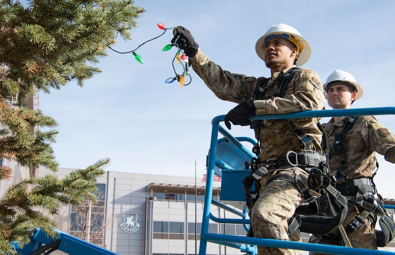 Airman 1st Class Vincent Henderson, left, 823rd Red Horse Civil Engineer Squadron electrical systems journeyman, and  Staff Sgt. Alex Peffer, right, 50th Civil Engineer Squadron electrical systems journeyman, place holiday lights on a tree in front of the headquarters building at Schriever Air Force Base, Colorado, Dec. 2, 2019. The team placed more than 800 colorful bulbs on the 40 foot tree. The 50th Space Wing will light the tree during an official lighting ceremony Dec. 5, 2019. (U.S. Air Force photo by Staff Sgt. Matthew Coleman-Foster)