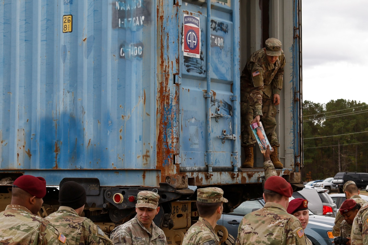 A soldier standing on the ground outside passes a toy to a soldier standing in a shipping-type container.