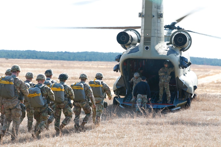 A group of soldiers load into a helicopter.