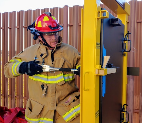 Photo shows firefighter using door simulator to practice forcible entry.