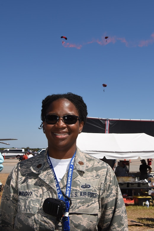 Photo shows Maj. LaToshia Wright, 2019 air show director, posing for a picture with the Army Black Daggers parachute jumpers performing in the background.