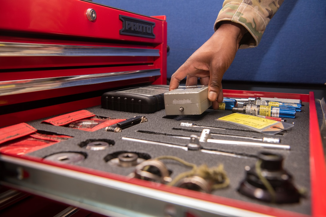 Tech. Sgt. Alexander Johnston, 100th Operations Support Squadron aircrew flight equipment lead trainer, retrieves a tool while repairing a piece of equipment at RAF Mildenhall, England, Dec. 3, 2019. Aircrew flight equipment Airmen inspect gear on a regular cycle to confirm it is free of defects. (U.S. Air Force photo by Airman 1st Class Joseph Barron)