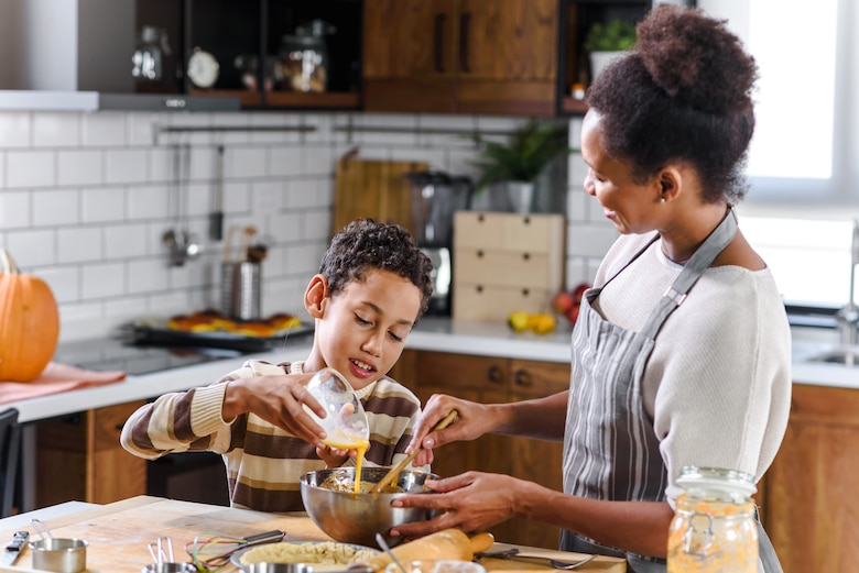 Photo shows mother and son preparing a pie.
