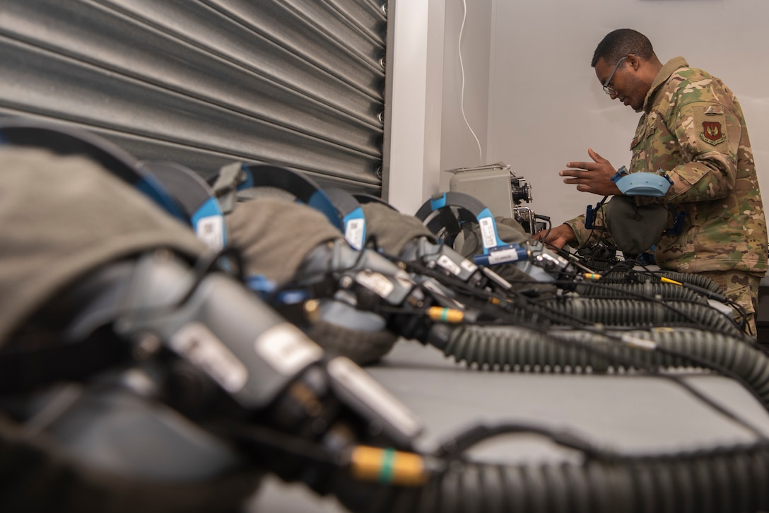 Tech. Sgt. Alexander Johnston, 100th Operations Support Squadron aircrew flight equipment lead trainer, tests a quick-don oxygen mask for functionality at RAF Mildenhall, England, Dec. 3, 2019. The AFE Airmen protect aircrew by ensuring their equipment is operational and free of defects. (U.S. Air Force photo by Airman 1st Class Joseph Barron)