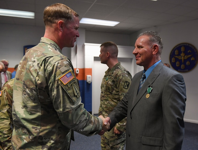U.S. Army Col. Bryan Morgan, 128th Aviation Brigade commander, congratulates William M. Storrs, Charlie Company, 1st Battalion, 210th Aviation Regiment, 128th Aviation Bde. instructor writer, during the Instructor of the Year ceremony at Joint Base Langley-Eustis, Virginia, Nov. 21, 2019.
