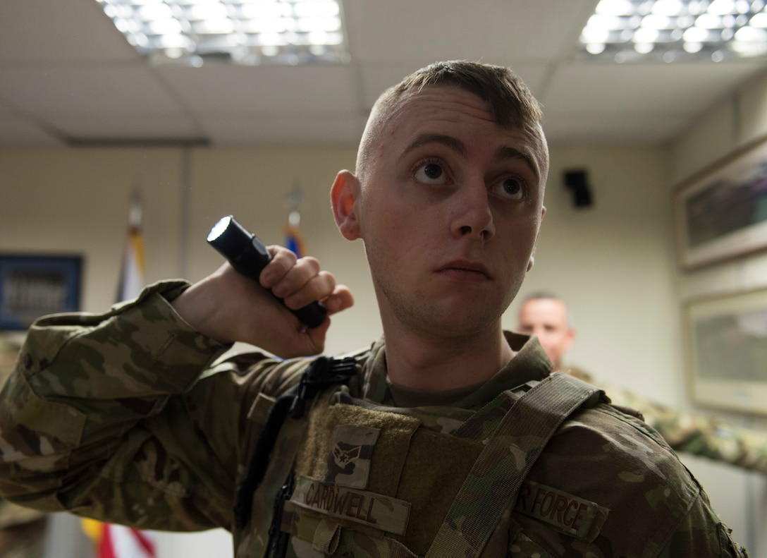 U.S. Air Force Airman 1st Class Christian Cardwell, 422nd Security Forces Squadron response force member, shines a flashlight during a recall exercise at RAF Croughton, England, November 21, 2019. Quarterly recall exercises are a form of readiness for defenders to always be prepared to respond at a moment's notice. (U.S. Air Force photo by Airman 1st Class Jennifer Zima)