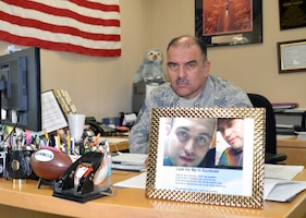 Chief Master Sgt. Pedro Saenz, a 433rd Aircraft Maintenance superintendent, sits at the desk in his office with his son's photo in the foreground and his son's favorite stuffed animal, the sloth in the background.