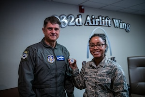 Tech. Sgt. Brandy Brown, religious affairs Airman, 932nd Airlift Wing Chaplain's Office, displays the Wing coin Col. Glenn Collins, 932nd AW commander, presented Brown after having shared her Airman's Story with Wing leadership during the the Wing Review meeting, Nov. 15, 2019, Scott Air Force Base, Illinois.  Each month before the unit training assembly a Citizen Airman shares some facts about their Air Force career,  civilian life, and goals within the Air Force Reserve. (U.S. Air Force photo by Christopher Parr)