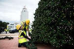 Rosa Padin, 502nd Civil Engineer Squadron secretary, helps decorate the base Christmas tree, Nov. 21, 2019, at Joint Base San Antonio-Randolph, Texas. Padin has volunteered to decorate all three trees of Joint Base San Antonio for the past four years. The trees are location on JBSA-Lackland, JBSA-Randolph, and JBSA-Fort Sam Houston. Along with making some of the decorations herself, Padin goes to each tree to coordinate where each decoration is positioned.