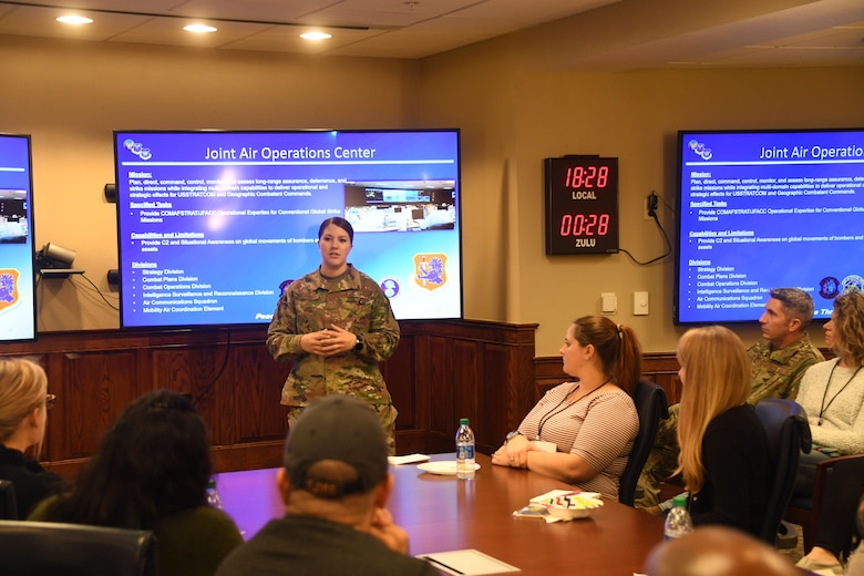 "Senior Airman Melissa Carlier, a member of the 608th Air Operations Center ISR division, describes her unit's mission and role within bomber operations during a spouses' orientation at headquarters 8th Air Force, Barksdale AFB, La., Nov. 18, 2019. More than 30 military spouses received an immersion briefing, toured the different centers and met with local leadership. ""The commitment and sacrifice it takes to be a military spouse is an honorable quality,"" said Chief Master Sgt. Melvina Smith, 8th Air Force command chief and J-GSOC senior enlisted leader. ""They provide an incomparable level of support, which ultimately affects unit readiness, personal resilience and quality of life."""