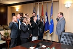 Eight new associates stand in front of flags with their right hand raised