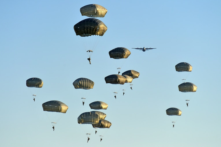 A group of soldiers with green parachutes descend in the sky after exiting an aircraft.