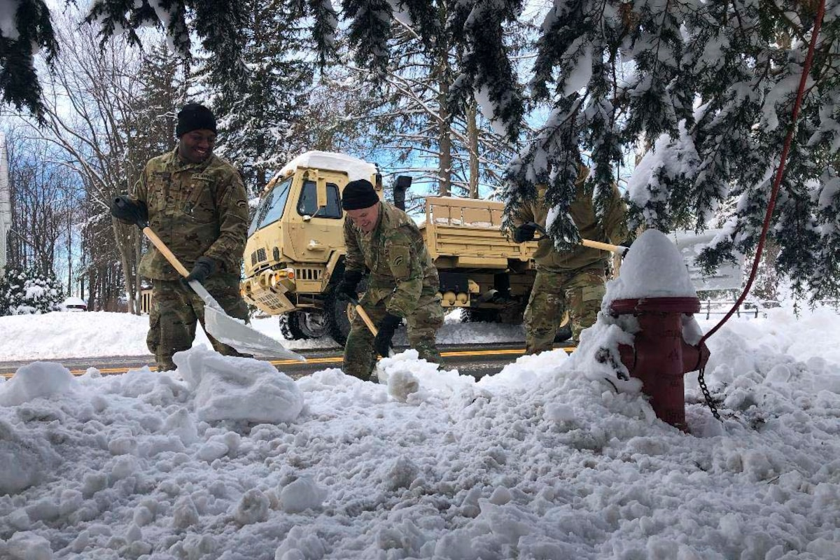Two soldiers use shovels to clear snow.