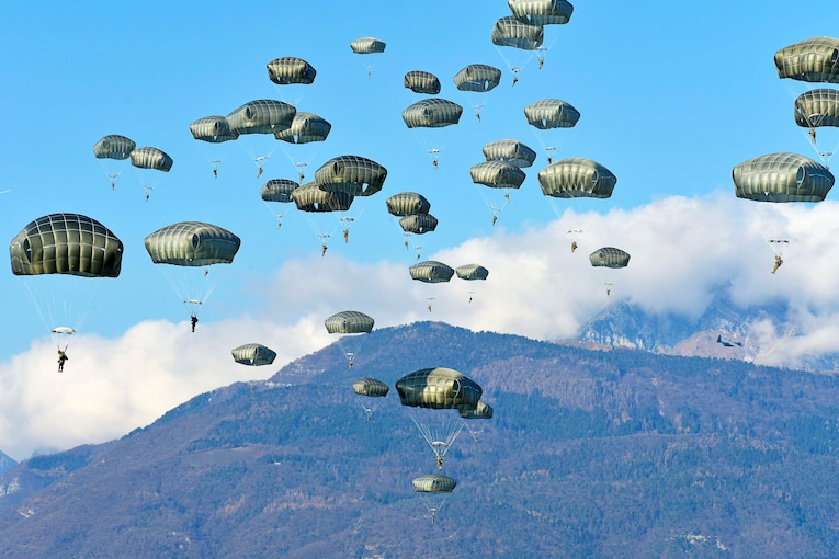 Soldiers descend through the sky wearing parachutes.