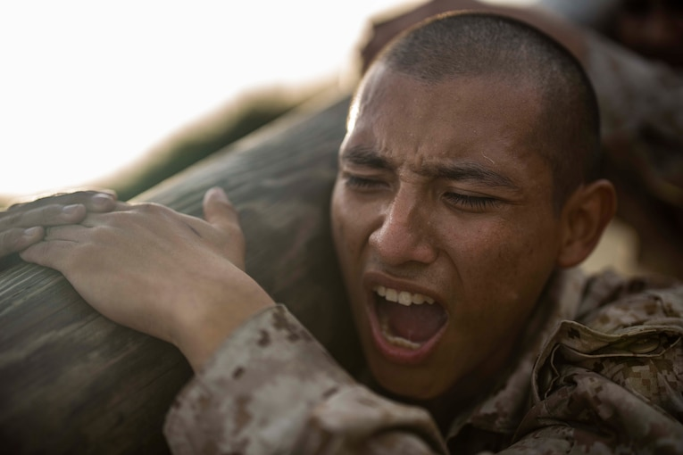 A Marine holds a log on his shoulder.