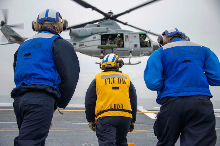Three sailors look up at a helicopter.