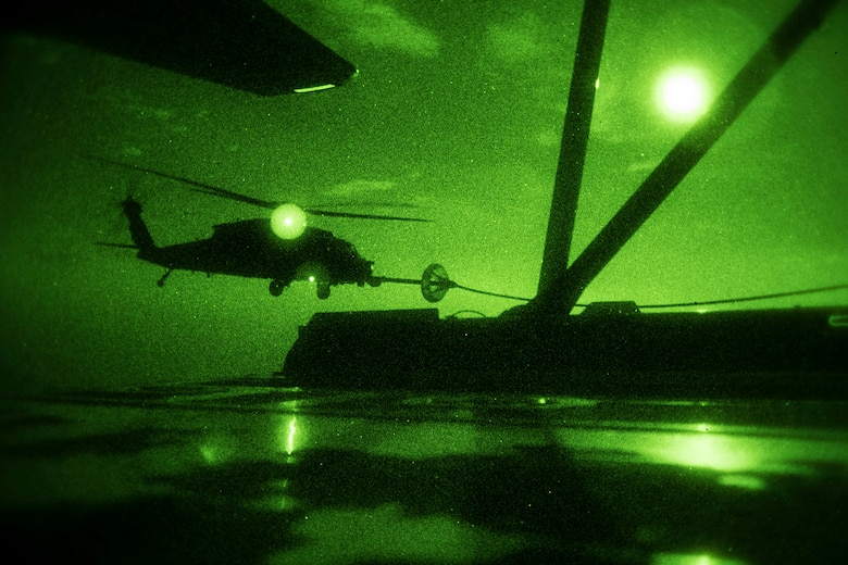 A night vision photo of a military rescue helicopter receiving fuel from a carrier aircraft.