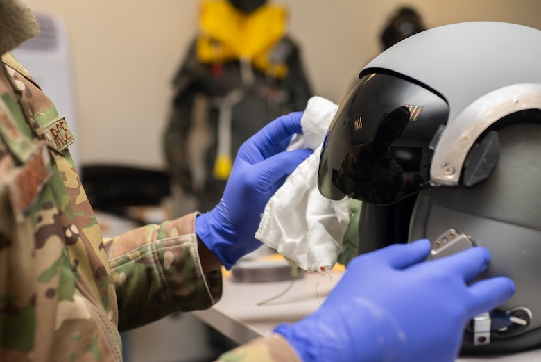Tech. Sgt. Alexander Johnston, 100th Operations Support Squadron aircrew flight equipment lead trainer, cleans a helmet visor at RAF Mildenhall, England, Dec. 3, 2019. The AFE shop maintains and inspects equipment such as flight helmets, oxygen masks, survival gear and radios that help pilots and other aircrew complete the mission. (U.S. Air Force photo by Airman 1st Class Joseph Barron)