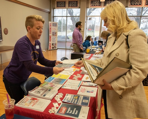 """Sara Bateman, Wright-Patt Base Exchange services business manager, shows a brochure to Shannon Carroll, Air Force Research Laboratory, information management lead, during the """"ThanksCIVing"""" Information Fair, hosted by the Affirmative Employment Program, inside the USO building at Wright-Patterson Air Force Base, Ohio, Nov. 21, 2019. Many information booths were set-up to share information about services and benefits available to Air Force civilian employees.  (U.S. Air Force photo by Michelle Gigante)"""