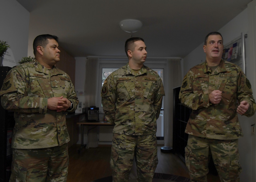 U.S. Air Force Brig. Gen. Mark R. August, 86th Airlift Wing commander, and Chief Master Sgt. Ernesto J. Rendon, 86th AW command chief, praise Senior Airman Eric Mrkonja, Deployment Transition Center lodging manager and vehicle control officer, at Ramstein Air Base, Germany, Nov. 25, 2019. Mrkonja is currently doing the workload performed by two noncommissioned officers, as a senior airman. (U.S. Air Force photo by Staff Sgt. Kirby Turbak)