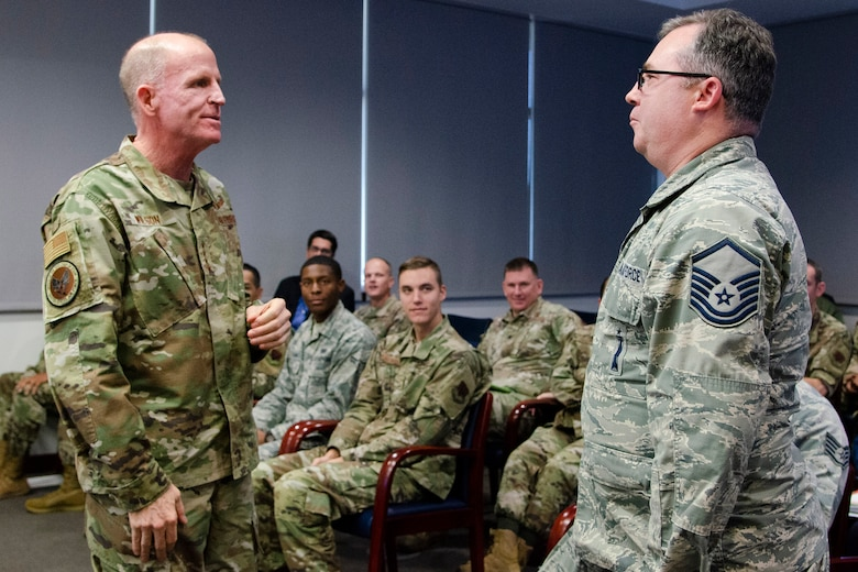 """Gen. Stephen W. """"Seve"""" Wilson (left), Air Force Vice Chief of Staff, presents his coin to Master Sgt. Ryan Doss, a mission director for the Air Force Technical Applications Center at Patrick AFB, Fla., after Doss was recognized as an outstanding performer by his chain of command.  Wilson visited the AFTAC Dec. 4, 2019 with Air Force Deputy Chief of Staff for Strategic Deterrence and Nuclear Integration Lt. Gen. Richard Clark for an in-depth look into how the nuclear treaty monitoring center accomplishes its global mission.  (U.S. Air Force photo by Susan A. Romano)"""