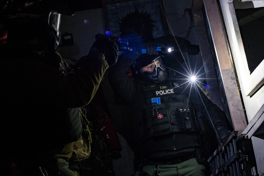 Ian Naylord, a SWAT team member with the Ardmore Police Department in Ardmore, Okla., works with Ardmore PD SWAT teammate Jared Johnson and a member of the 137th Special Operations Security Forces Squadron to tactically advance past a window during an active shooter scenario at SWAT training with the Oklahoma County Sheriff's Office in Oklahoma City on Nov. 7, 2019. (U.S. Air National Guard photo by Staff Sgt. Brigette Waltermire)