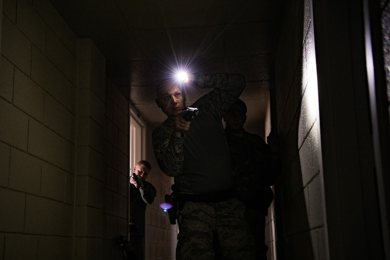 Four participants in SWAT training conducted by the Oklahoma County Sheriff's Office slowly work to clear a dormitory rooms in a hallway while looking for an instructor who is acting as an armed threat at Southern Nazarene University in Bethany, Okla., on Nov. 5, 2019. The two SWAT team members from Ardmore Police Department in Ardmore, Okla., secured the hallway as two members of the 137th Special Operations Security Forces Squadron approach a doorway. 