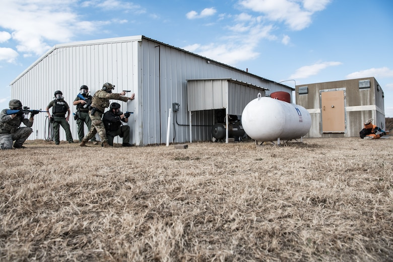 A team of Ardmore Police Department SWAT members and 137th Special Operations Security Forces Squadron Airmen use the end of a building as protection while they simulate engagement with a possible suspect with a gun during SWAT training conducted by the Oklahoma County Sheriff's Office at the OCSO training range in Spencer, Okla., Nov. 4, 2019. (U.S. Air National Guard photo by Staff Sgt. Brigette Waltermire)