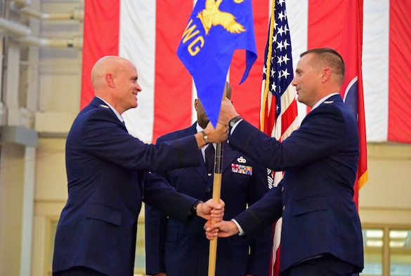 U.S. Air Force Col. Jason Glass, left, the assistant adjutant general of the Tennessee Air National Guard, passes the guide-on flag to Col. Todd Wiles, right, the incoming commander of the 118th Wing, at a wing change of command ceremony Nov. 3, 2019 at Berry Field Air National Guard Base, Nashville, Tennessee.